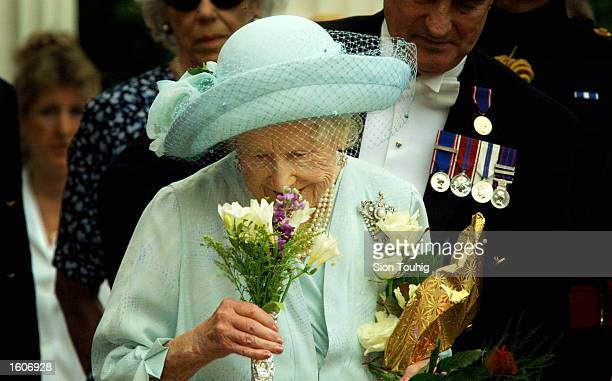 Britain''s Queen Mother smells flowers she received during celebrations to mark her 101st birthday August 4 2001 in London
