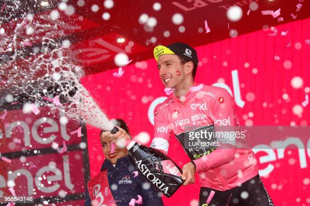 Britain's rider of team MitcheltonScott Simon Yates celebrates the pink jersey of the overall leader on the podium after the 10th stage between Penne...
