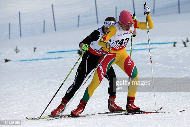 Britain's Rosamund Musgrave and Lithuania's Diana Rasimoviciute compete on February 20 2013 during the women's World Cup FIS Nordic skiing cross...