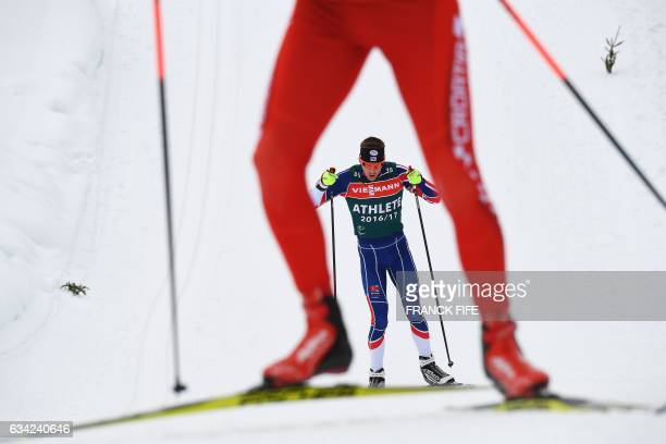 Britain's Scott Dixon is seen through the legs of another athlete as he takes part in a the training session on the eve of the 2017 FIS Biathlon...