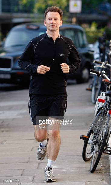 Britain's Secretary of State for Culture Media and Sport Jeremy Hunt jogs near his London home on May 25 2012 British Prime Minister David Cameron...