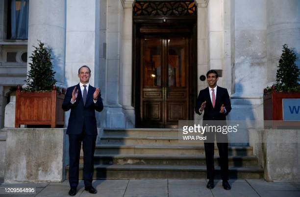 Britain's Secretary of State for Foreign Affairs Dominic Raab and Britain's Chancellor of the Exchequer Rishi Sunak applaud during the Clap For Our...