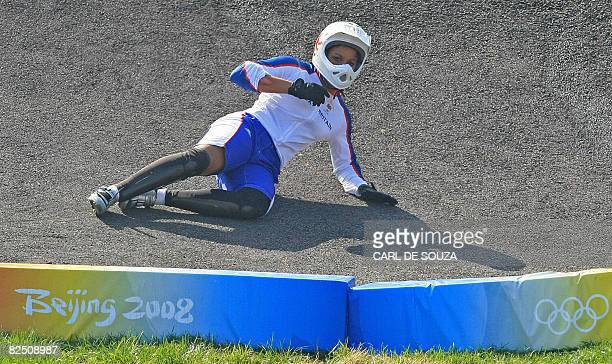 Britain's Shanaze Reade slides after falling from her bike during a semi-final heat in the women's BMX finals at the 2008 Beijing Olympic Games at...