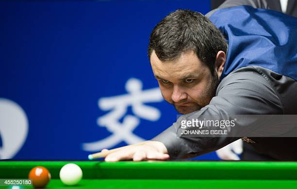 Britains Stephen Maguire plays a shot against Britain's Alan McManus during the second round of the Snooker Shanghai Masters in Shanghai on September...