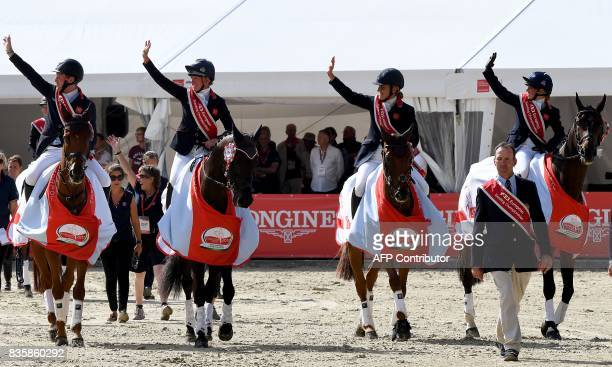 Britain's team wave as they come for the medal ceremony of the FEI European Eventing Championships in Strzegom Poland on August 20 2017 after they...