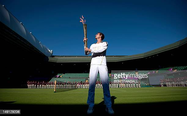Britain's tennis player Andy Murray carries the Olympic Torch in Centre Court at the Olympic tennis venue in the All England Tennis Club in Wimbledon...