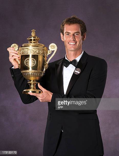 Britain's tennis player Andy Murray poses with the 2013 Wimbledon trophy during the Wimbledon Champions Dinner in central London on July 8 a day...