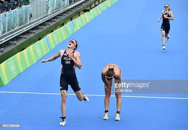 Britain's Vicky Holland crosses the finish line to win the bronze medal next to the recovering silver medalist Switzerland's Nicola Spirig and fourth...