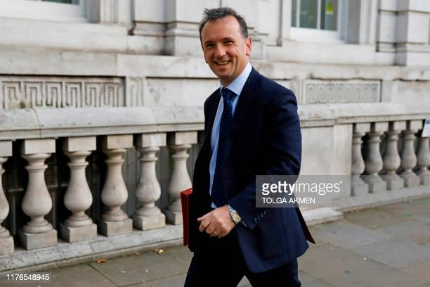 Britain's Wales Secretary Alun Cairns smiles as he walks down Whitehall in central London on October 18 2019 British Prime Minister Boris Johnson...