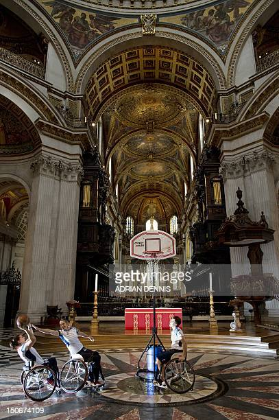 Britain's wheelchair basketball players Sarah Grady Judith Hamer and Helen Turner practice under the dome in St Paul's Cathedral in London on August...