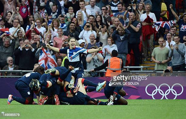 Britain's women's football team celebrate after scoring an opening goal against Brazil in their London 2012 Olympic Games preliminary round Group E...