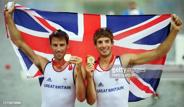Britain's Zac Purchase and Mark Hunter celebrate on the podium during the medals ceremony for the lightweight men's double sculls at the Shunyi...