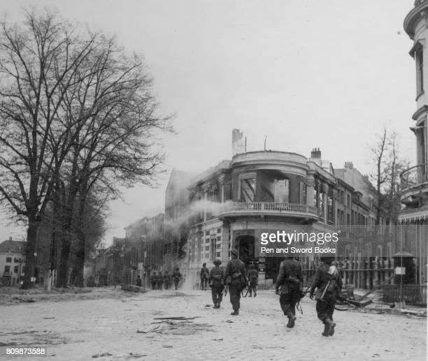 Brithish troops in Arnhem next smouldering buildings.