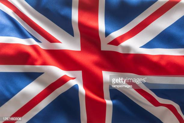 brithish uk flag blowing in the wind. - union jack stock pictures, royalty-free photos & images