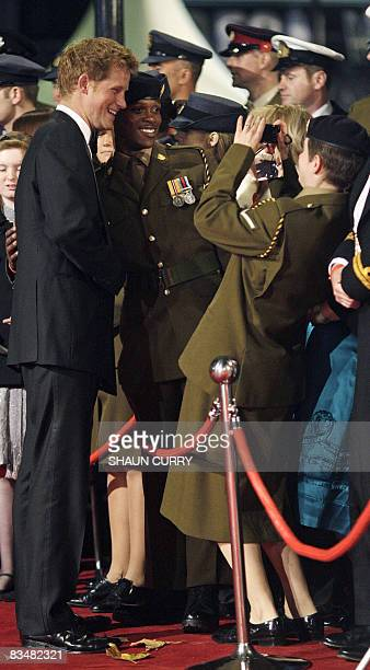"""Britiain's Prince Harry of Wales poses with military service personnel as he attended the World Premiere of the new James Bond film """"Quantum of..."""