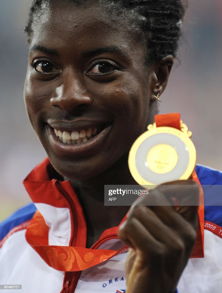 Britian's gold medalist Christine Ohuruogu poses on the podium after the women's 400m final at the 'Bird's Nest' National Stadium during the 2008 Beijing Olympic Games on August 19, 2008. Christine Ohuruogu of Great Britain won the 400 metres women's Olympic title here on Tuesday in a time of 49.62seconds. The 24-year-old world champion beat home Shericka Williams of Jamaica (49.69sec) while favourite Sanya Richards of the United States took bronze (49.93sec).