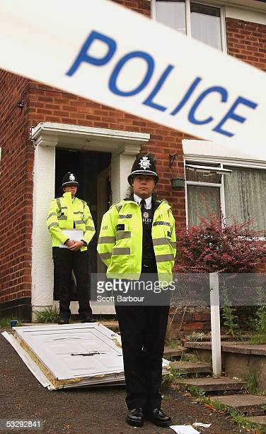 Britiish police officers stand outside at a house in Washwood Heath raided in connection with investigations into the London bombings on July 27 2005...