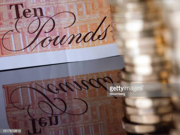 A British 10pound banknote and one pound sterling coins sit in this arranged photograph in London UK on Wednesday Aug 15 2018 The pound's weakness is...