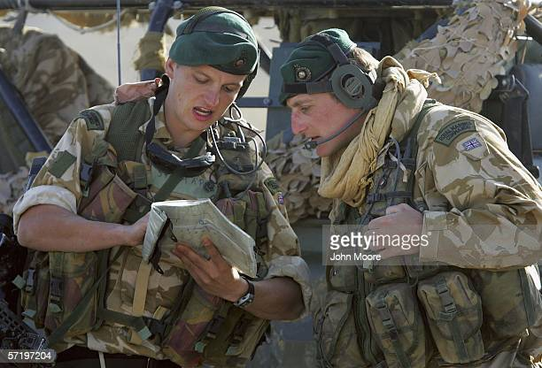 British 2nd Lt Gordon Sweny from the 42 Royal Marines reads over a map with a fellow marine near Camp Bastion in the desert of Helmand Province in...