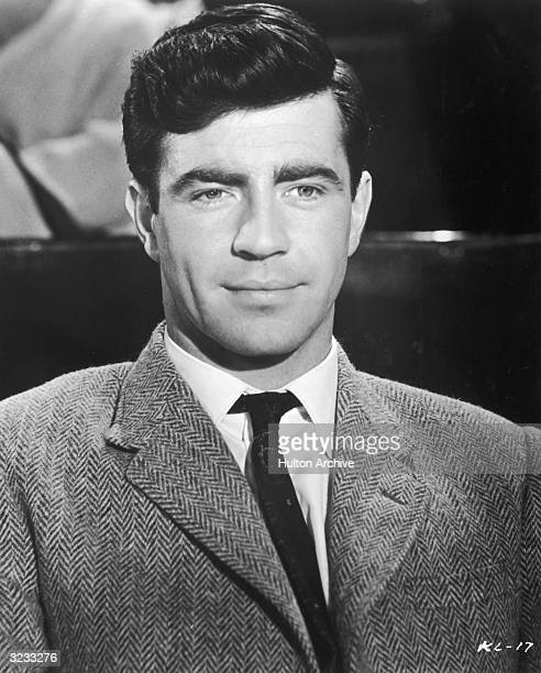 British actor Alan Bates wearing a tweed jacket and a tie smiles in still from director John Schlesinger's film 'A Kind of Loving'