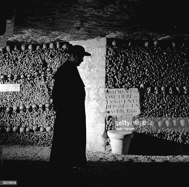 British actor Alec Guinness on location in the catacombs of Paris during filming of 'Father Brown' in which he plays G K Chesterton's famous priest...