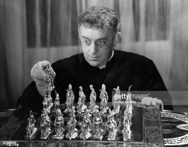 British actor Alec Guinness plays G K Chesterton's famous crimesolving priest in the eccentric comedy 'Father Brown' as he ponders over a chess...