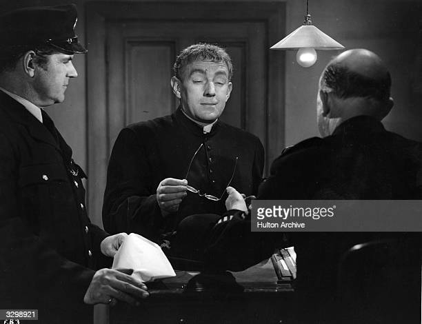 British actor Alec Guinness plays G K Chesterton's famous crimesolving priest in the eccentric comedy 'Father Brown' as he confronts a couple of...