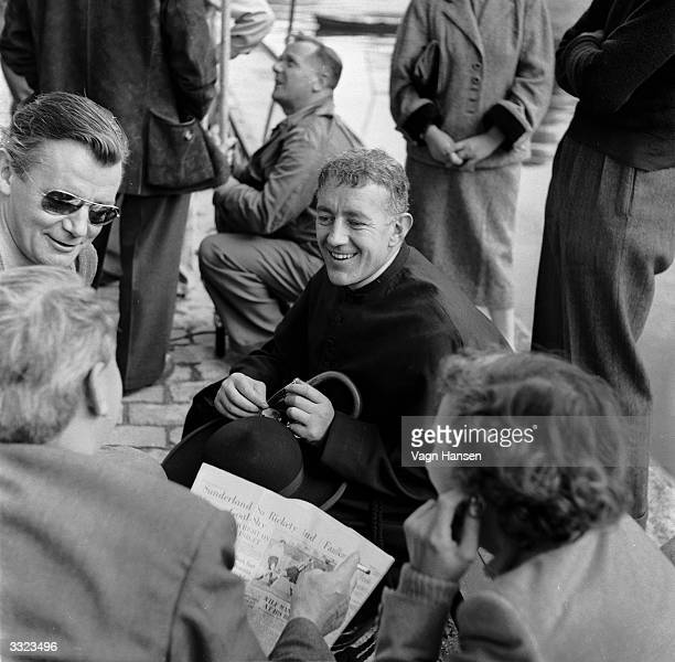 British actor Alec Guinness talks to locals whilst on location in Paris for the filming of 'Father Brown' in which he plays G K Chesterton's famous...