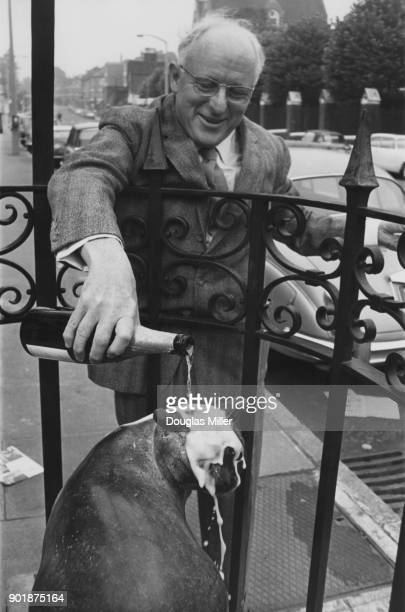 British actor and children's author Donald Bisset pours champagne over a statue of Dick Whittington's cat on Highgate Hill London 23rd August 1967...
