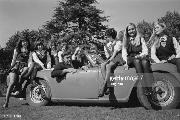 British actor and comedian Frankie Howerd with a group of young actresses on the set of the comedy film 'The Great St Trinian's Train Robbery', UK,...