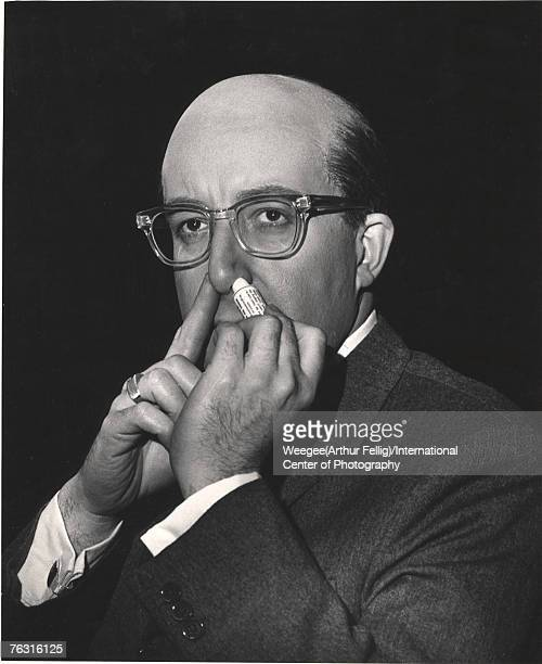 British actor and comedian Peter Sellers in costume as American President Merkin Muffley uses a nasal inhaler on the set of the Stanley Kubrick film...