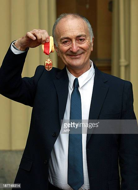 British actor and comedian Tony Robinson holds his medal after being knighted by the Duke of Cambridge during an investiture ceremony at Buckingham...