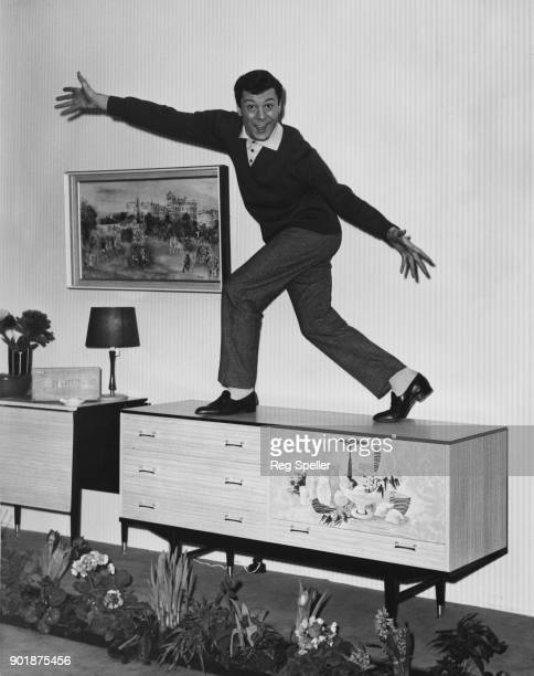 British actor and dancer Lionel Blair demonstrates the hardwearing nature of a melamine surface by dancing on top of a Berry sideboard at the...