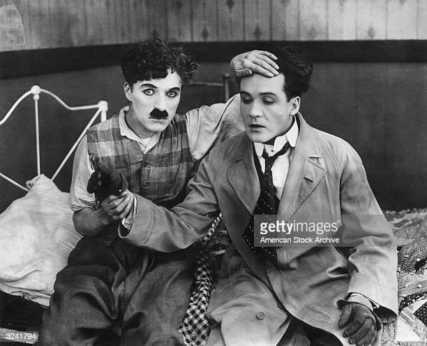 British actor and director Charles Chaplin holding British actor Tom Terriss's wrist while feeling his forehead in a still from director Chaplin's...