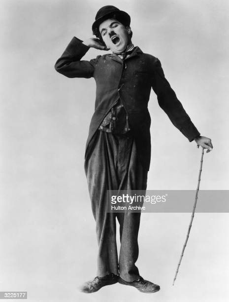 British actor and director Charlie Chaplin stretches and yawns in a fulllength promotional portrait for his film 'The Tramp'