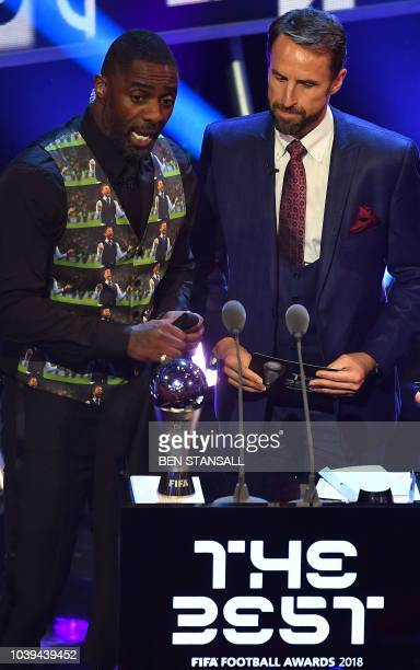 British actor and event host Idris Elba wearing a Gareth Southgate waistcoat chats with England's coach Gareth Southgate during The Best FIFA...