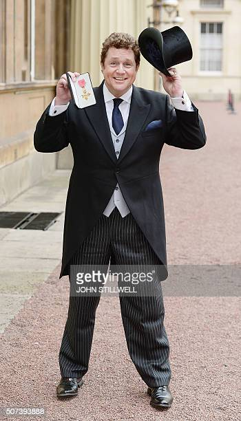 British actor and singer Michael Ball, poses for a photograph with his Officer of the Order of the British Empire medal, after being presented with...