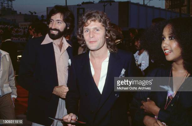 British actor and singer Paul Nicholas, wearing a blue double-breasted jacket over a white shirt, open at the neck, stands between two unspecified...