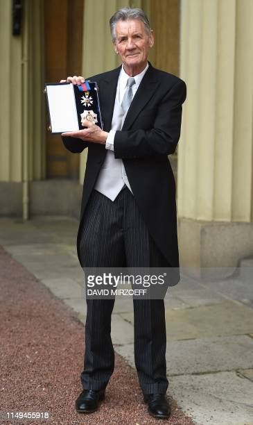 British actor and television presenter Michael Palin poses with his medals after being appointed a Knight Commander of the Order of St Michael and St...