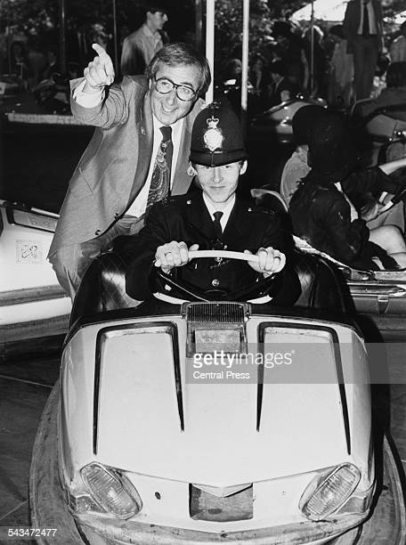 British actor and television presenter Shaw Taylor is given a ride on a bumper car by Police Constable Paul Harvey at the Belgave Fair in aid of the...
