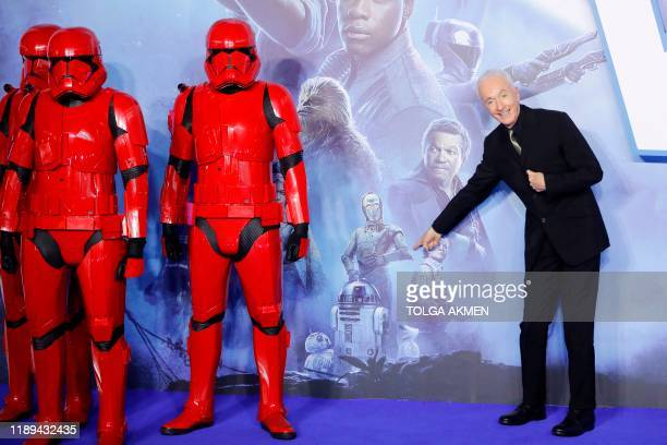 British actor Anthony Daniels poses with sith stormtroopers on the red carpet upon arrival for the European film premiere of Star Wars The Rise of...