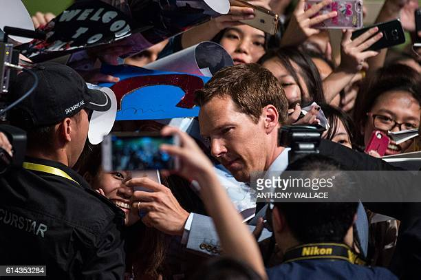 British actor Benedict Cumberbatch poses for a selfie with a fan as he arrives for a red carpet event to promote his latest movie Marvel's Doctor...