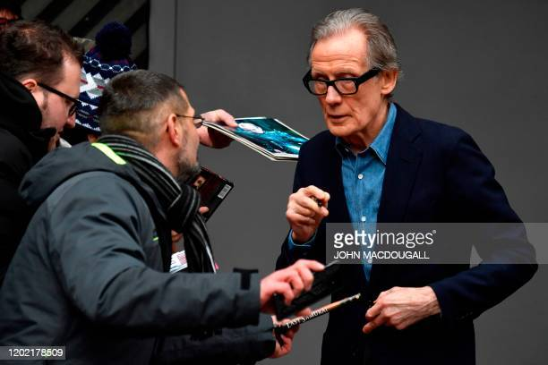 British actor Bill Nighy signs autographs as he arrives for a photocall and press conference for the film Minamata screened in the Berlinale Special...