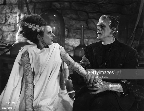 British actor Boris Karloff holds the hand of British actor Elsa Lanchester in a still from director James Whale's film 'The Bride of Frankenstein'