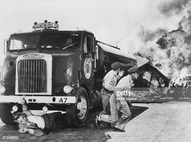 1959 British actor Cary Grant attempts to crawl out from under an exploding oil truck while the drivers flee in a still from director Alfred...