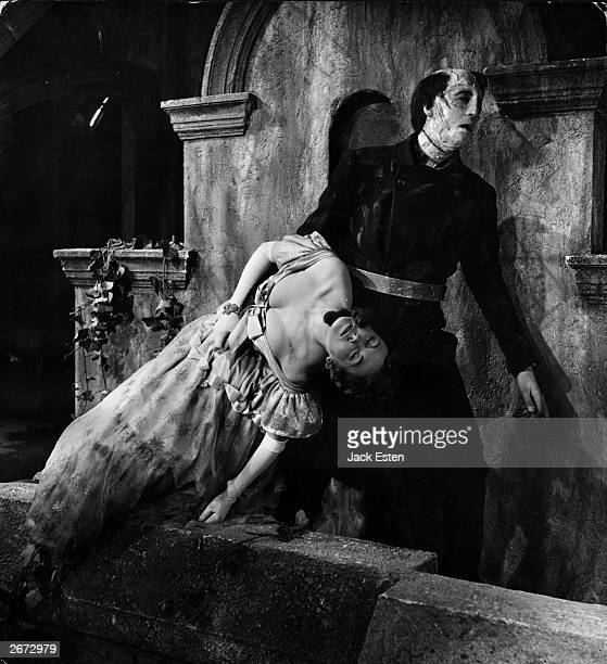 British actor Christopher Lee drags an unconscious woman across the set in the role of Frankenstein's monster in the Hammer horror film 'The Curse of...