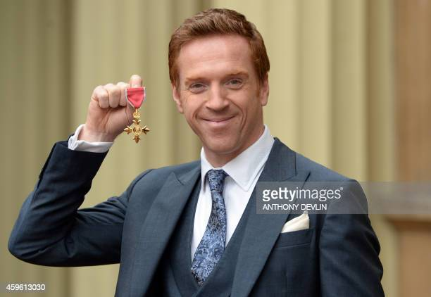 British actor Damian Lewis holds his Officer of the Order of the British Empire medal after an investiture ceremony at Buckingham Palace in London on...