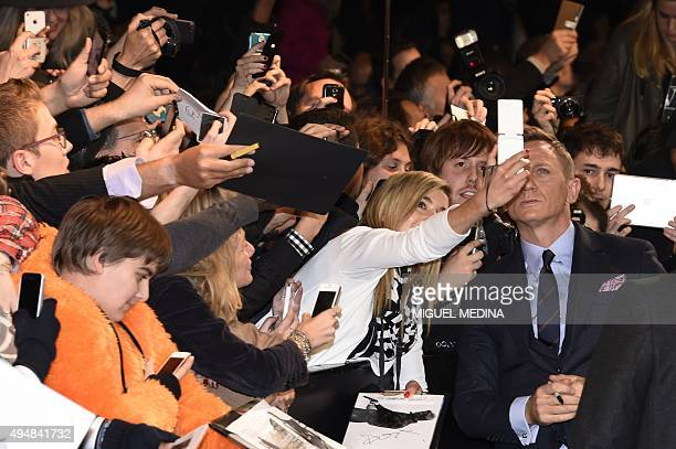 British actor Daniel Craig poses for a selfie with fans during the French premiere of the new James Bond film 'Spectre' on October 29 2015 in Paris...