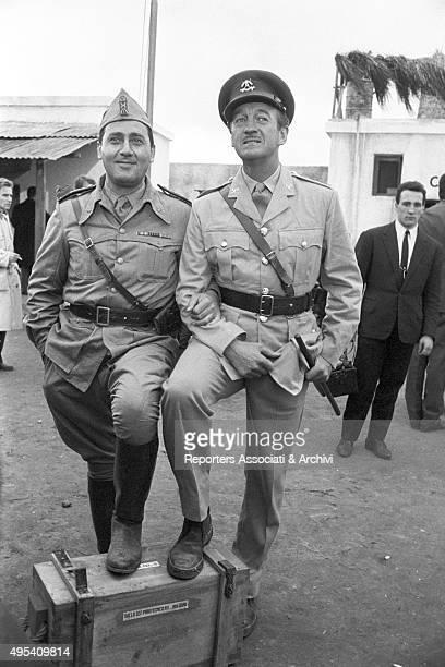 British actor David Niven smiling and hugging Italian actor Alberto Sordi on the set of the film The Best of Enemies 1961