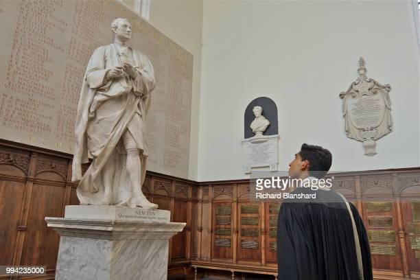 British actor Dev Patel as Indian mathematician Srinivasa Ramanujan admiring the statue of Isaac Newton at Trinity College Cambridge in a scene from...